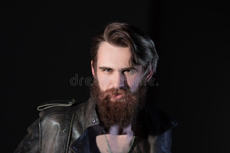 Smiling bearded man hipster in leather jacket royalty free stock photos