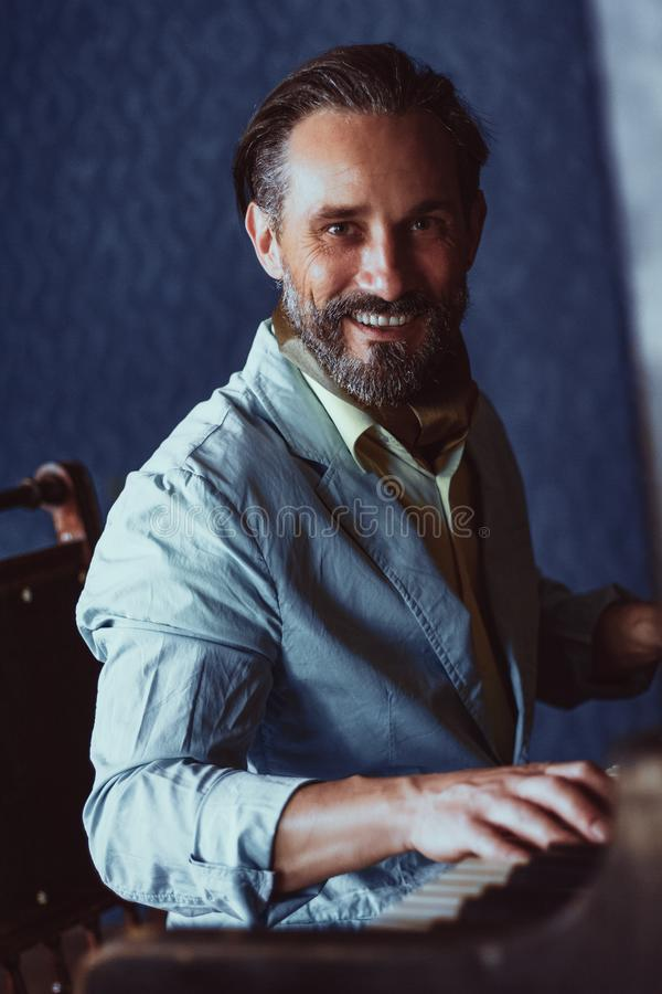 Handsome musician composes music sitting at piano stock images