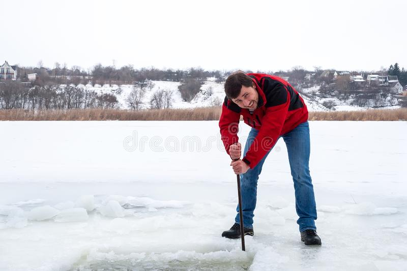 Smiling bearded man in a red jacket and jeans pierces the ice on the frozen river with a crowbar royalty free stock images