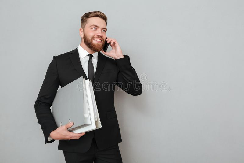 Smiling bearded man in suit talking on the smartphone royalty free stock images