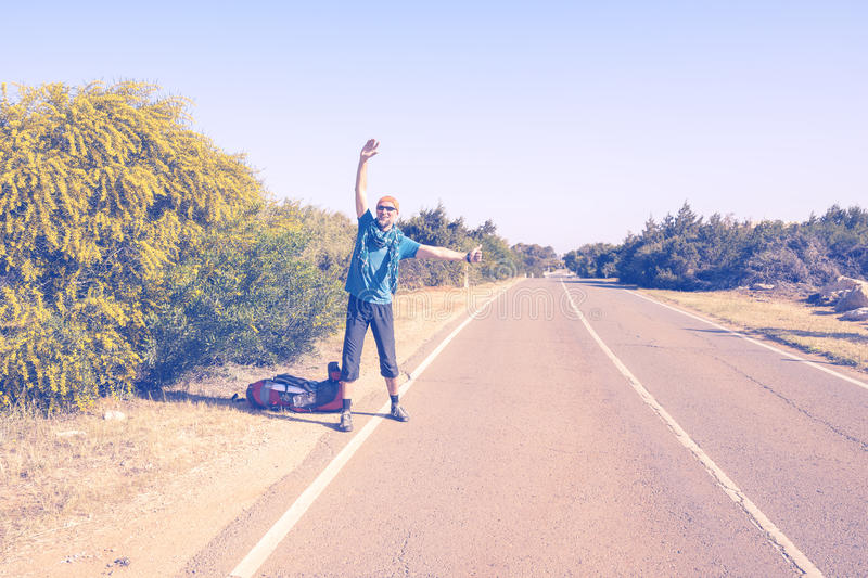 Smiling bearded man traveling hitchhiking. Smiling bearded man with backpack is traveling hitchhiking, stands on road sunny day, waiting for a passing car. Toned stock photo