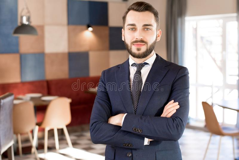 Smiling bearded manager in restaurant hall royalty free stock images