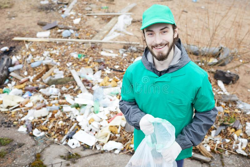 Cheerful volunteer with rubbish bag. Smiling bearded volunteer in green uniform holding bag for litter and looking at camera royalty free stock images