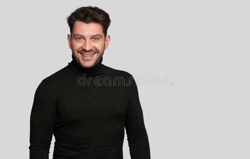 Smiling bearded young male model dressed casually. Isolated over white background. Positive pleased guy being in good mood. Man in black turtleneck royalty free stock image