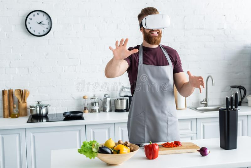 smiling bearded young man in apron using virtual reality headset while cooking in kitchen royalty free stock images