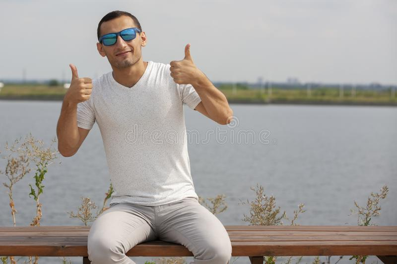 Smiling bearded young man showing thumbs up. Cheerful handsome young man gesturing outdoor stock photo