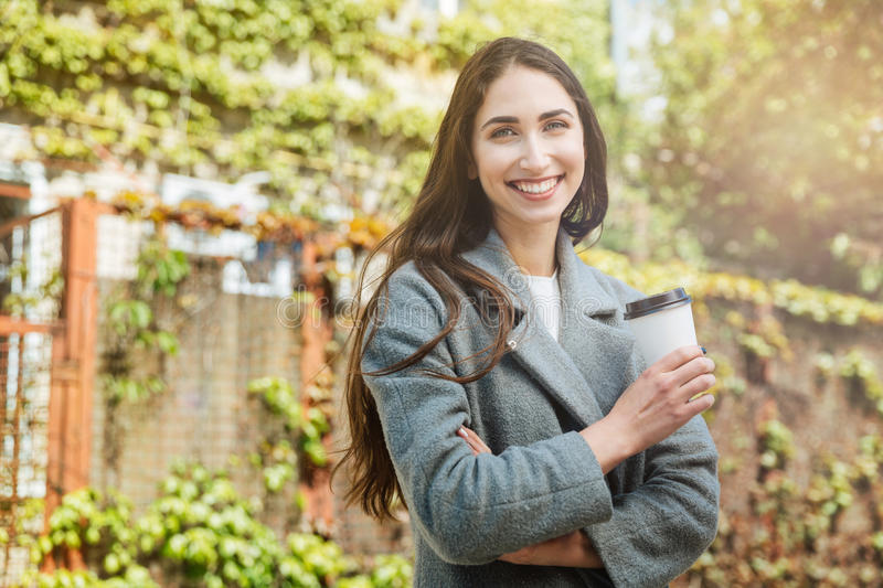 Smiling beauiful cheerful girl holding take away coffe. Cup outdoors royalty free stock image