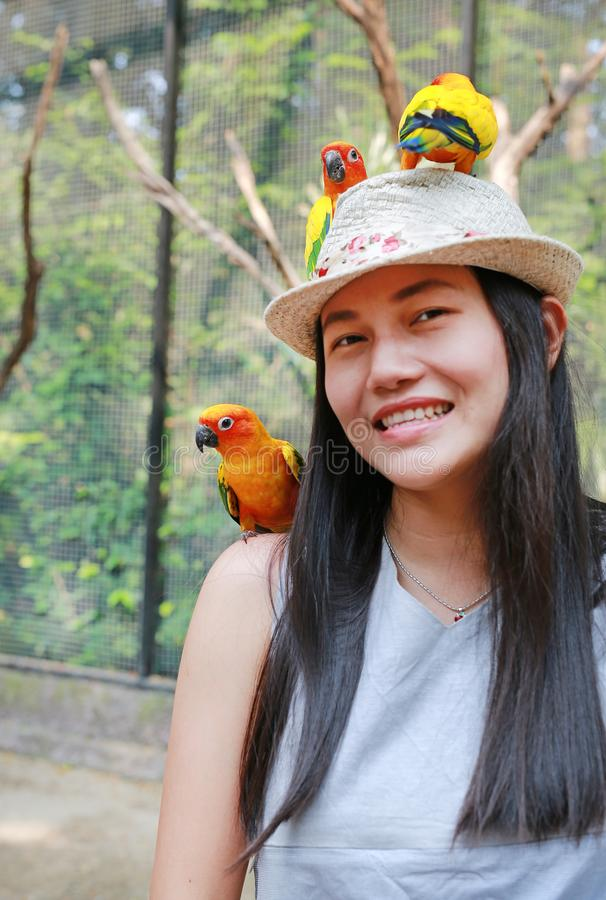 Smiling of beautiful Asian woman playing with sun conure parrots royalty free stock photo