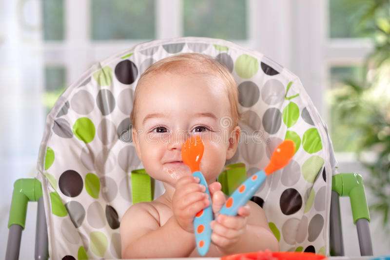 Smiling beautiful baby eating with spoon and fork stock images