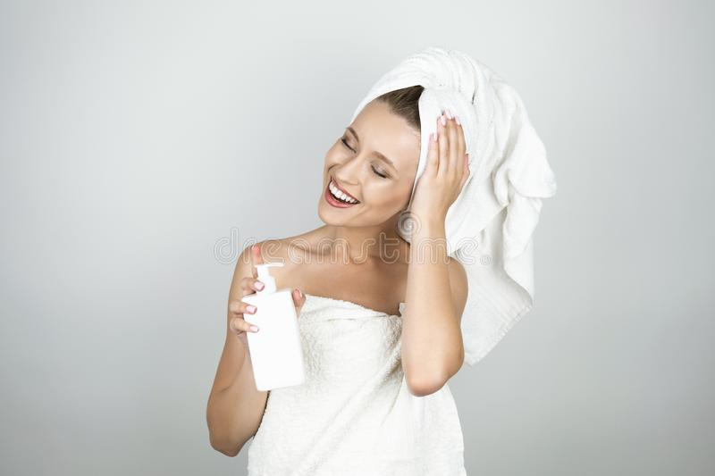 Smiling beautiful blond woman in white towel over body and on her head holding body lotion isolated white background royalty free stock photos