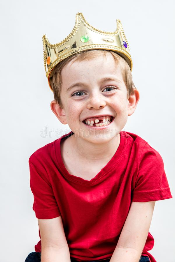 Smiling beautiful boy with golden crown and missing tooth posing. Portrait of a smiling beautiful 7-year old boy with a golden crown and a missing tooth posing stock photos