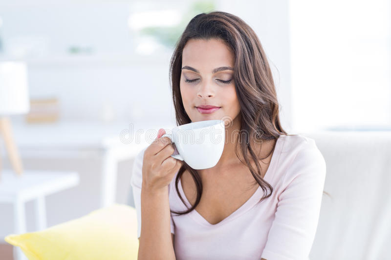 Smiling beautiful brunette relaxing on the couch and holding mug stock photo