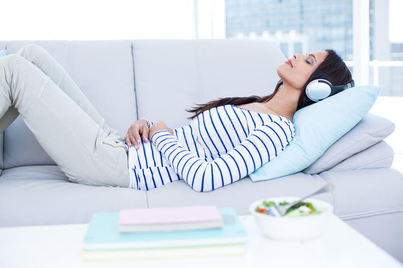 Smiling beautiful brunette relaxing on the couch and listening music. In the living room royalty free stock photo