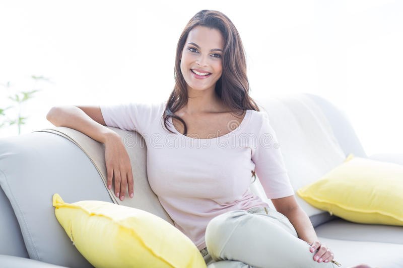 Smiling beautiful brunette relaxing on the couch and looking at camera. In the living room stock photography