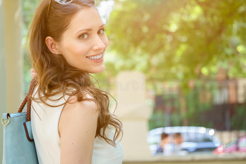 Smiling beautiful brunette woman looks back. Closeup portrait of smiling beautiful brunette woman looks back. Image with lens flare effect stock images