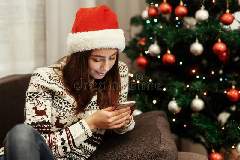 Smiling, beautiful brunette woman in red santa claus hat and white reindeer sweater browsing on her smartphone, while sitting on. A comfy couch near decorated royalty free stock photos