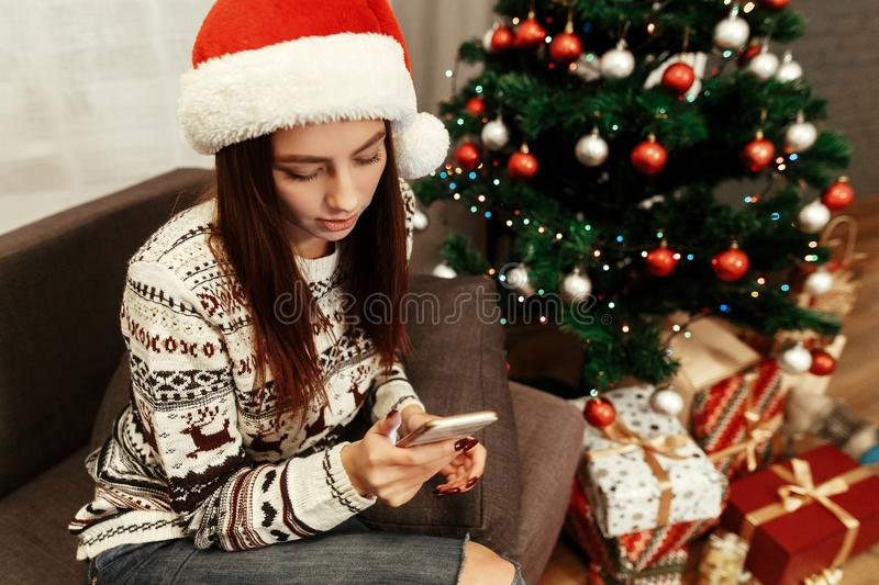 Smiling, beautiful brunette woman in red santa claus hat and white reindeer sweater browsing on her smartphone, while sitting on. A comfy couch near decorated stock image