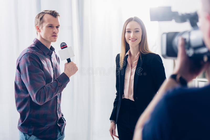 Smiling beautiful businesswoman in suit giving interview to journalist and looking at camera. In office royalty free stock images