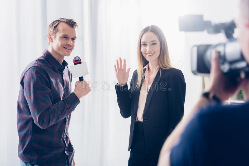 Smiling beautiful businesswoman in suit giving interview to journalist and waving hand. In office royalty free stock images