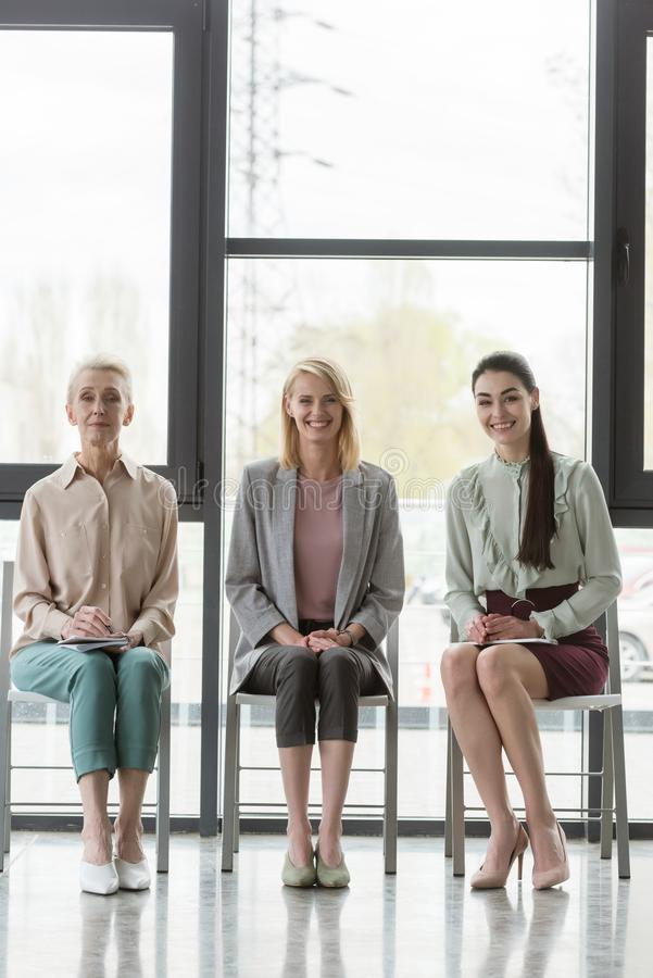 smiling beautiful businesswomen sitting on chairs during meeting stock photo