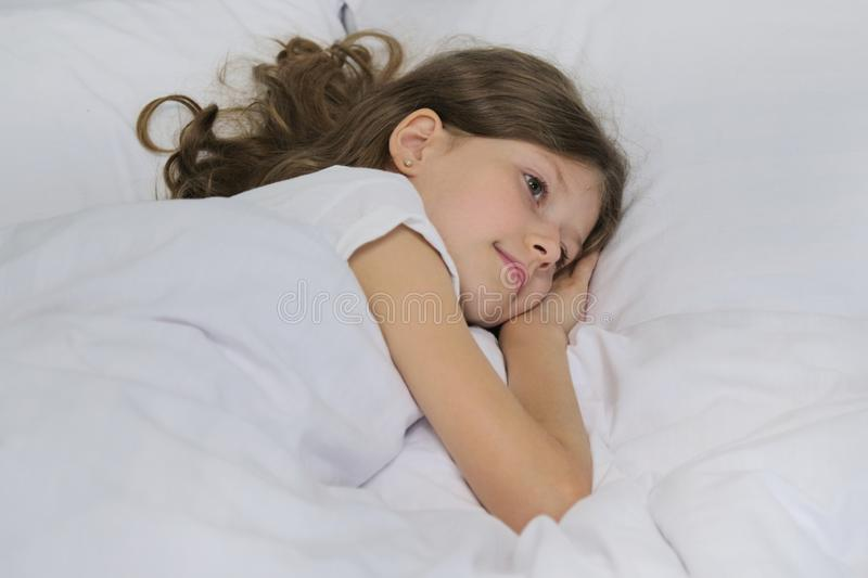Smiling beautiful child girl lying on a pillow, white bed, close-up face royalty free stock image