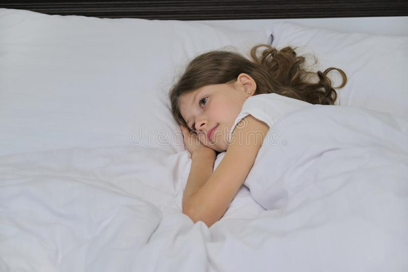 Smiling beautiful child girl lying on a pillow, white bed, close-up face stock photography