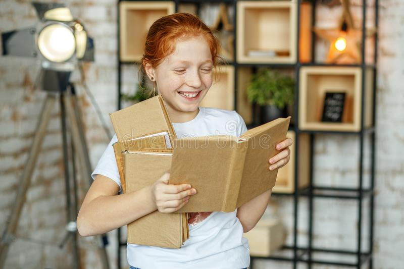 Smiling beautiful child holds a lot of books. The concept of lif stock photo
