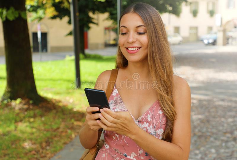 Smiling beautiful fashion woman typing with phone in the street royalty free stock photos