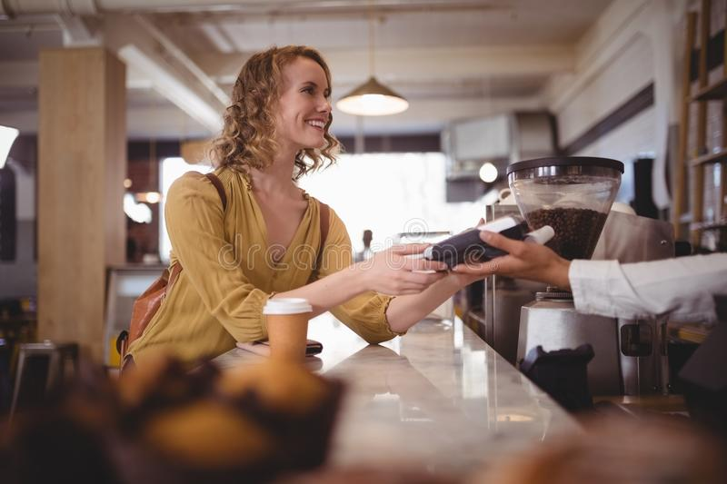 Smiling beautiful female customer paying through card at counter. In coffee shop royalty free stock photos