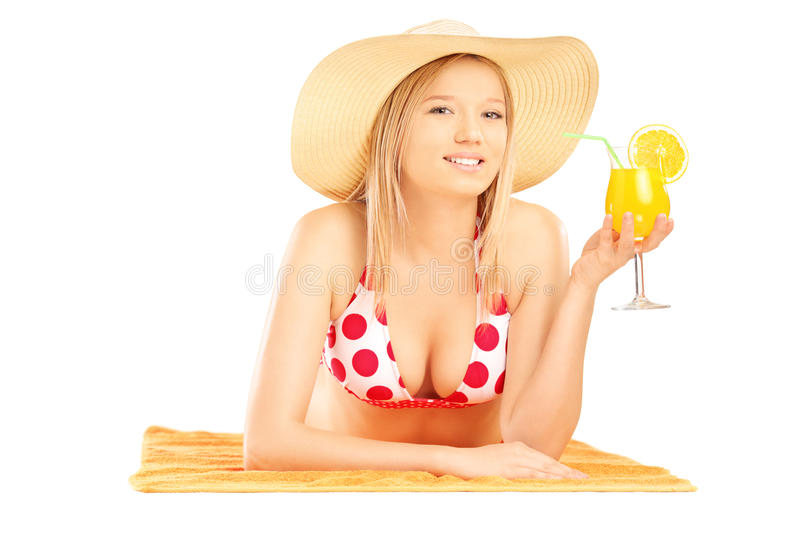 Smiling beautiful female with hat lying on a beach towel and drinking cocktail royalty free stock photo