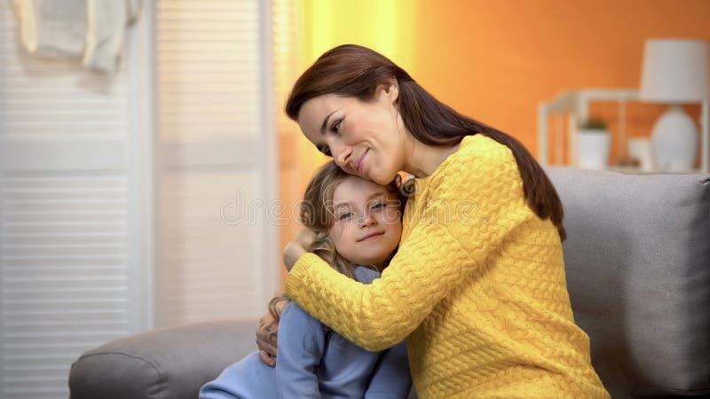 Smiling beautiful female hugging tenderly happy preschool daughter, trust royalty free stock image