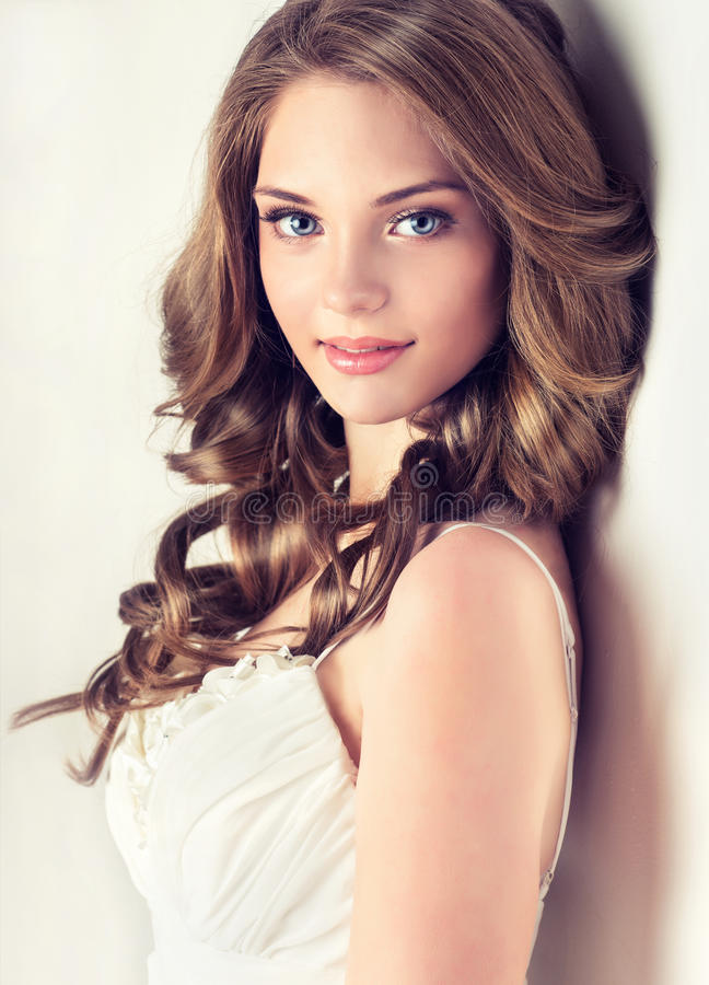 Smiling Beautiful girl, brown hair with an elegant hairstyle , hair waves ,curly. royalty free stock images