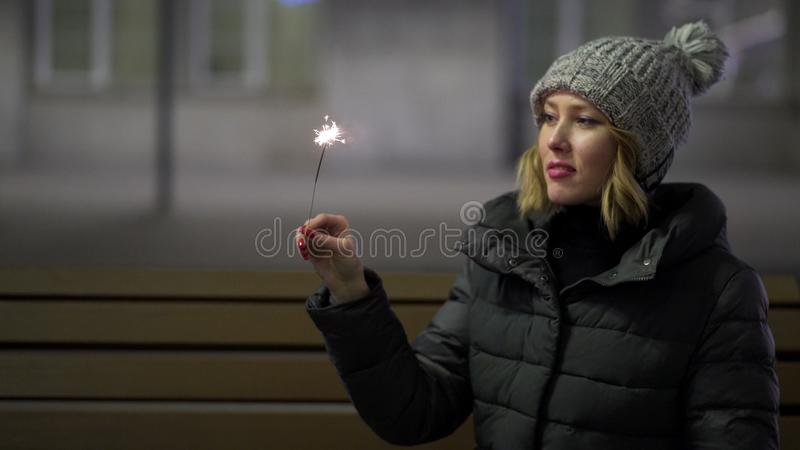 Smiling, beautiful girl in knitted hat and down jacket in the street at night with sparkler, celebrating New year, Merry stock photography