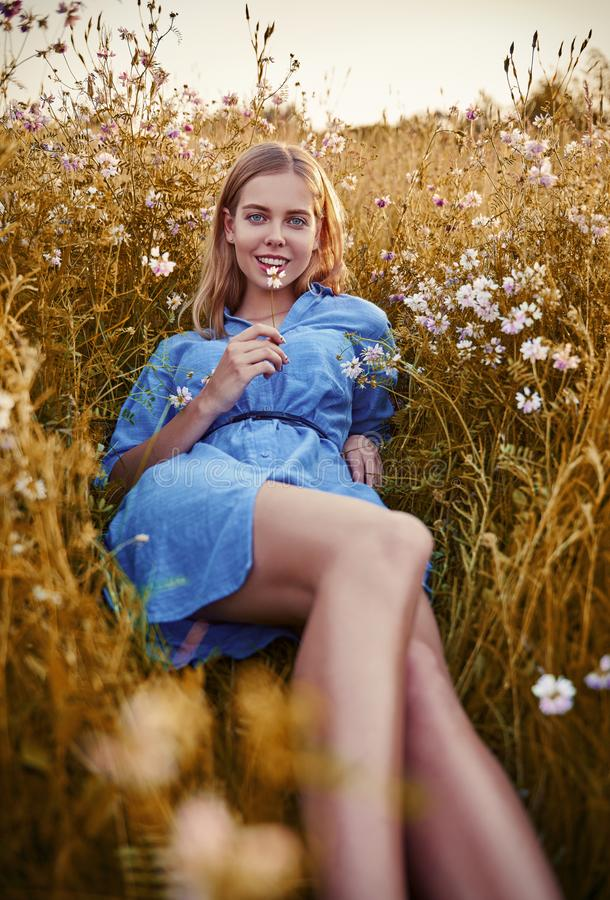 Smiling beautiful girl lying among grass and flowers. Outdoor portrait of attractive young woman in blue dress stock photography