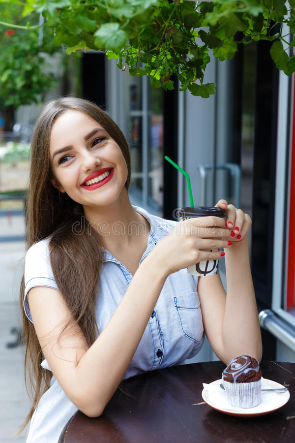 Smiling beautiful girl in outdoor cafe drinking coffee with muf stock photo