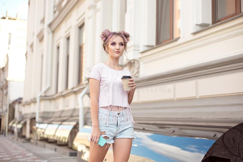 Smiling beautiful girl with pink hair hairstyle walks down the street with a cup of coffee enjoying a beautiful sunny. Day royalty free stock images