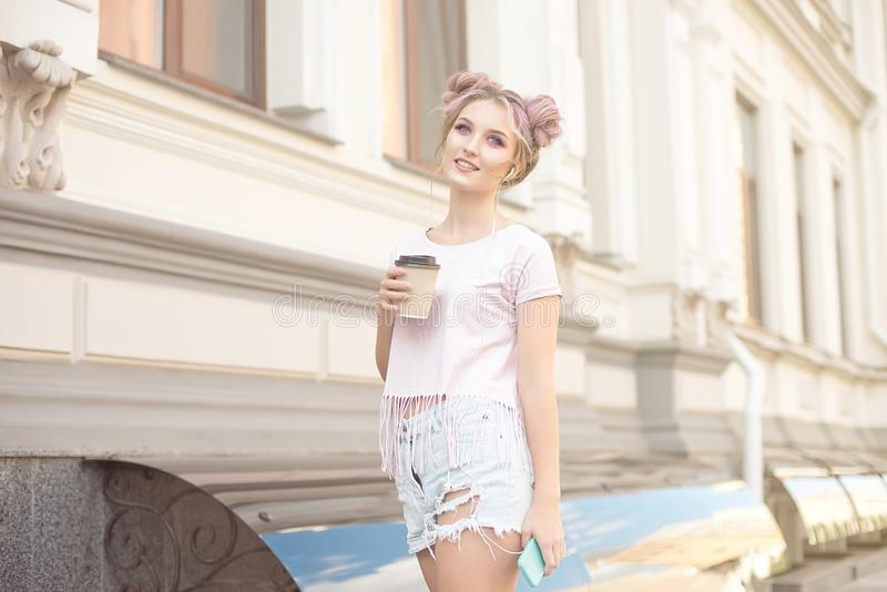 Smiling beautiful girl with pink hair hairstyle walks down the street with a cup of coffee enjoying a beautiful sunny royalty free stock photo