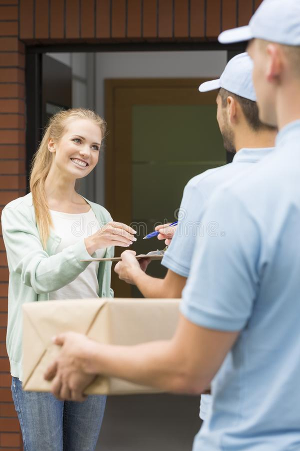 Girl and two couriers in blue uniforms stock photos