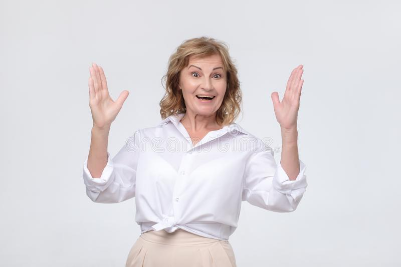 Smiling beautiful mature woman making hands the size of big thing royalty free stock photos