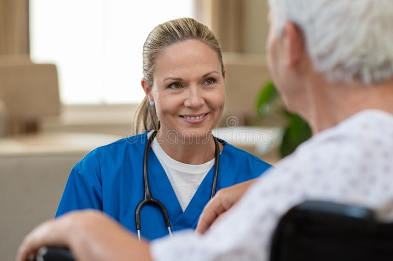 Nurse take care of senior patient. Smiling beautiful nurse in front of patient on wheelchair at hospital. Young friendly doctor consoling disabled senior man stock image