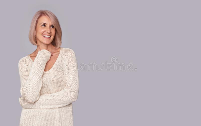 Smiling beautiful old woman looking up stock photo