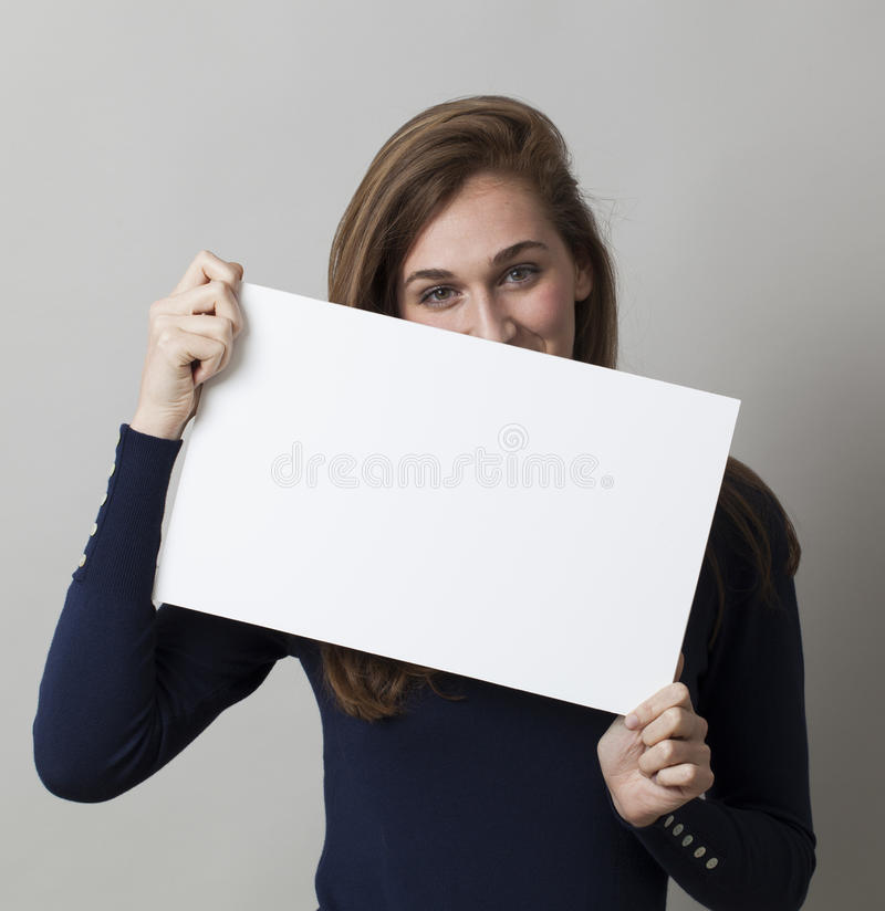 Smiling beautiful 20s woman enjoying hiding herself behind a blank banner for shyness about beauty royalty free stock photos