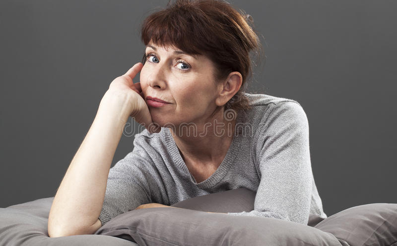 Smiling beautiful senior woman lying down on cushions with contentment. Satisfaction and smile concept - thinking 50s woman leaning on her hand and elbow,lying royalty free stock photos