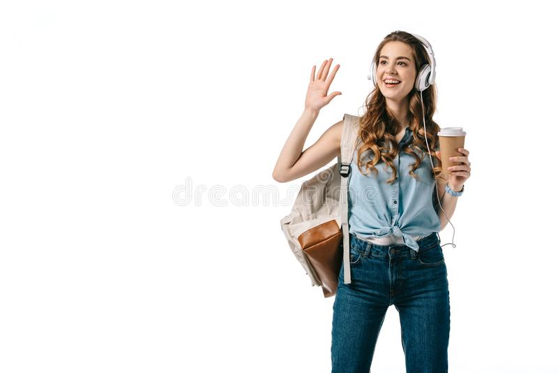smiling beautiful student waving hand and listening to music royalty free stock image