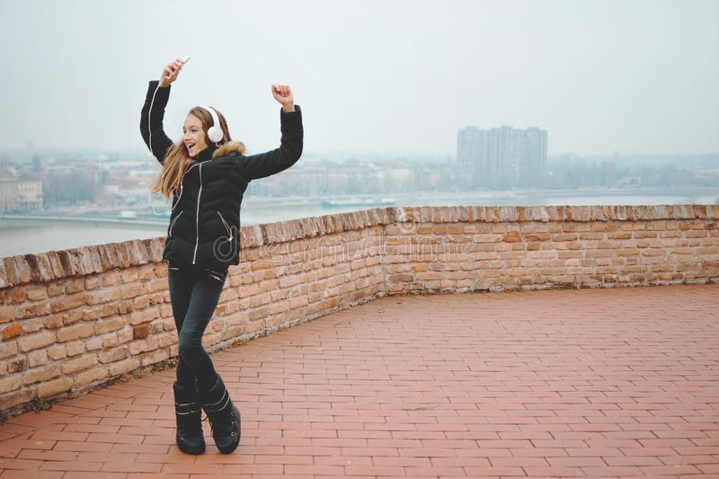 Smiling beautiful teenage girl listen to the music and dance with hands up outside royalty free stock photo