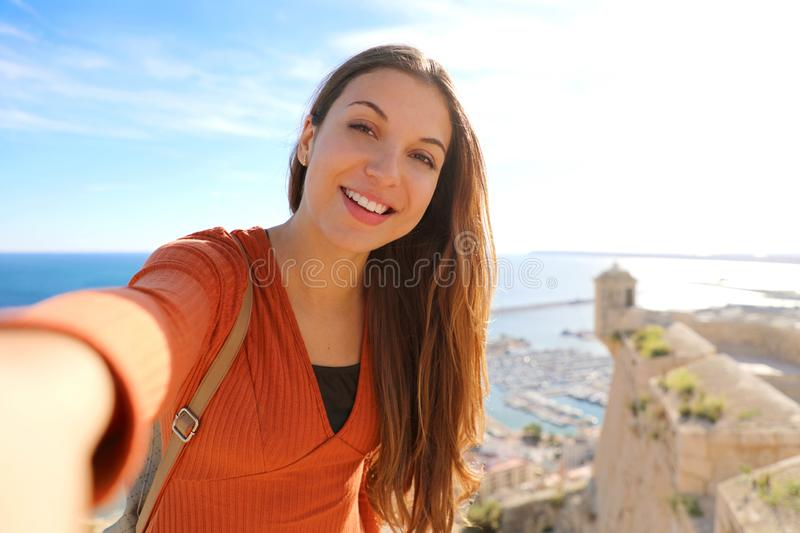 Smiling beautiful tourist woman taking selfie photo in Alicante, Spain. Traveler girl taking self portrait on Santa Barbara castle royalty free stock photo