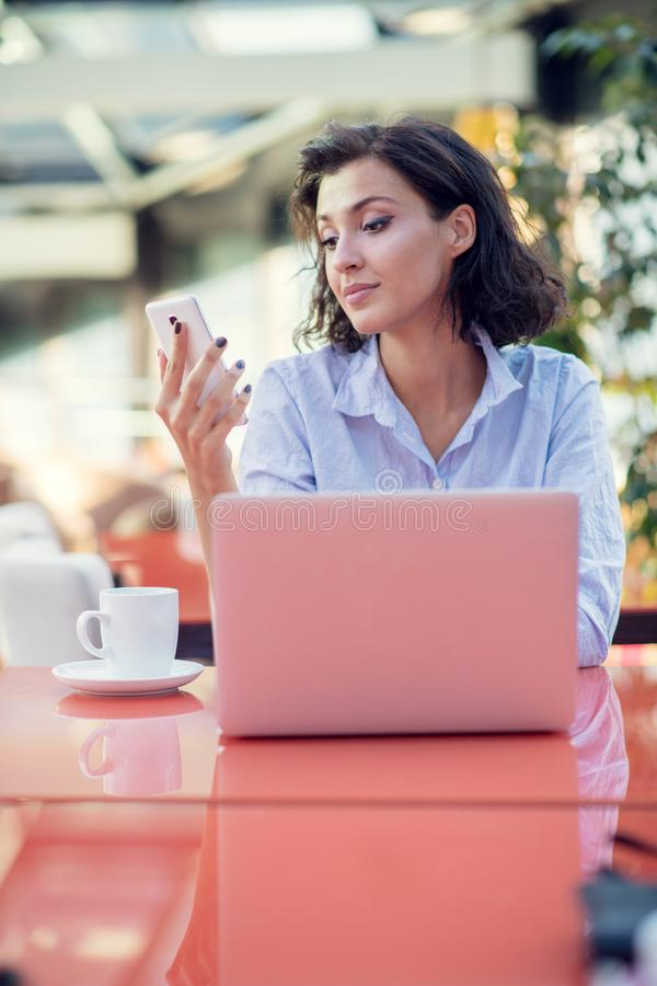 Smiling beautiful white caucasian girl with black curly hair sitting in street bar and using her phone. royalty free stock photography