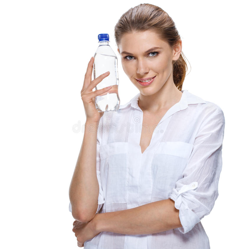 Smiling beautiful woman with bottle of water isolated on white. Compelling girl of the european appearance in a white shirt holds a transparent plastic bottle of royalty free stock photography