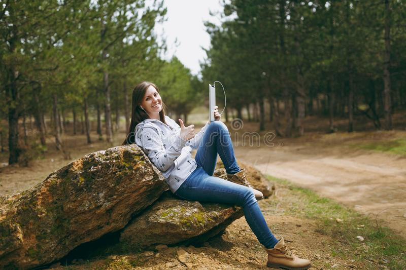 Smiling beautiful woman in casual clothes with earphones sitting on stone using tablet pc computer and showing thumb up. In city park or forest on green royalty free stock images