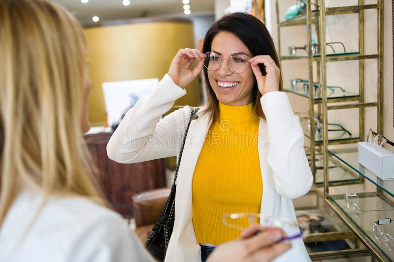 Smiling beautiful woman choosing and showing eyeglasses to attractive young oculist in optic shop stock photo